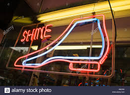 colorful neon light sign in NYC shoe repair store window Stock