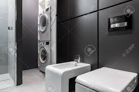 waschküche mit waschmaschine und trockner im modernen badezimmer