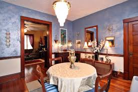 Craftsman Blue Dining Room With Elegant Set Of Lights And Hardwood Floors