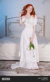 elegant woman with long red curly hair in white vintage elegant