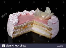 Slice of white cake with pink icing on a black background Stock Image