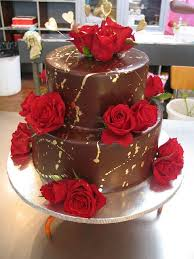 Wicked chocolate cake iced in chocolate ganache decorated with gold paint splatter fresh red roses & gold wired hearts by Charly s B