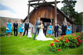 Bride And Groom Pose Outside Of Rustic Wedding Venue With Party