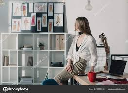 bureau de styliste élégant styliste assis sur table bureau regardant croquis