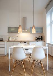 white and wood kitchen and dining table with eames chairs plus ena