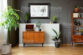 vintage schrank mit grammophon in echtes foto dunklen wohnzimmer interieur mit formteil und poster an wand frische pflanzen und dekoration