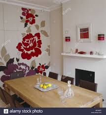 A Modern Dining Room With Simple Fireplace Painted Floral Mural On Wall Wood Table Leather Chairs