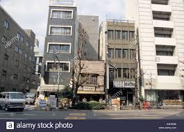 japan tokyo old shop wedged between two modern buildings stock