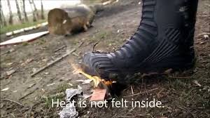 testing damage proof rubber boots holding muddy boot in fire