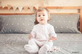 foto auf lager porträt süßen entzückenden kaukasischen blondine lächelnd baby mädchen in weißen onesie sitzt auf dem bett im schlafzimmer und