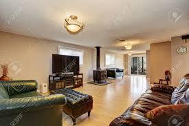 wohnzimmer mit antiken kamin ledersofas und hocker hellbraune holzboden und beige wände northwest usa