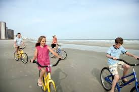 Family Bike Riding On The Beach In City Of Myrtle