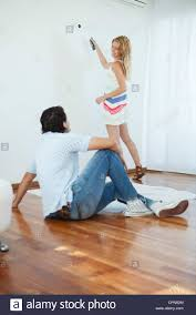 Man Watching Woman Painting Wall Using Paint Roller