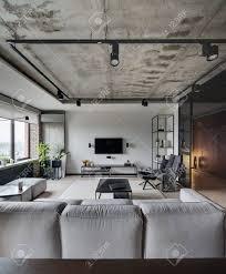 loft stil wohnzimmer mit weißen ziegel und betonwänden es gibt ein sofa tische stühle sessel regale lautsprecher fernseher und ein gestell