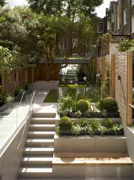 Photo Of A Contemporary Partial Sun Garden In London With Potted And Concrete Paving