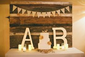 Simple Rustic Wedding Cake Display With A Wooden Backdrop
