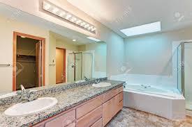 helles und luftiges badezimmer mit whirlpool und oberlichtern großem waschtisch mit zwei waschbecken granitablagen und braunem vinylboden