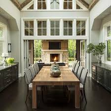 Dining Room With Vaulted Ceilings And Folding Glass Doors That Open To Patio