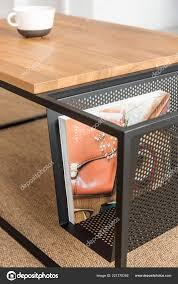 zeitung metallkorb neben holztisch auf teppich