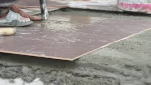 asian worker putting ceramic tile on the floor with cement stock