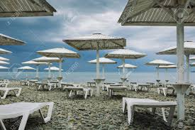 100 Wooden Parasols Parasols And Empty Deckchairs On Deserted Beach On The