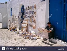 Man Reading Newspaper Beside Traditional Handicrafts