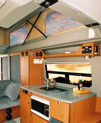 An Interior View Of A Custom Sportsmobile Sprinter Camper Conversion Van With The Penthouse Top Exanded