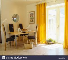 Yellow Curtains And Limestone Flooring In Modern Dining Room With Tall Back Chairs At Simple