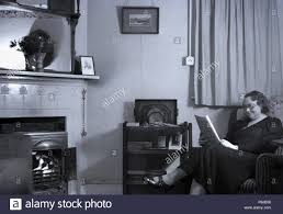 1950s, Lady Sitting In A Chair Reading A Newspaper In Her Front Room ...