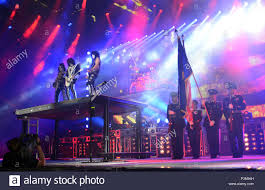 Members Of The Oregon Army National Guard Display American Flag On Stage While Band KISS Performs Anthem During Freedom To Rock