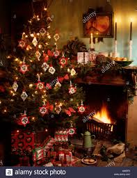 Close Up Of Gifts Below Christmas Tree With Home Made Cross Stitch Decorations Beside Fireplace In Cottage Living Room