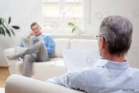 foto auf lager zwei reife männer die in einem wohnzimmer sitzen und zeitung lesen