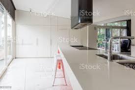 moderne weiße küche mit inselbank und terrazzoboden stockfoto und mehr bilder arbeitsplatte