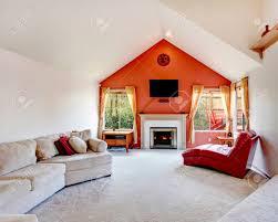 helles wohnzimmer mit weiß und orange wand decke vauled beige teppichboden kamin mit roter stuhl ohne armlehnen und beige machen es gemütlich