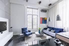 industriedesign im wohnzimmer mit fernseher und blau möbelset