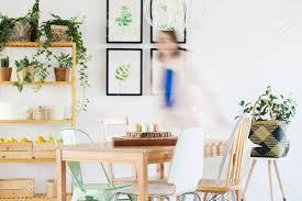 neues esszimmer mit holztisch stühlen bücherregal und pflanzen