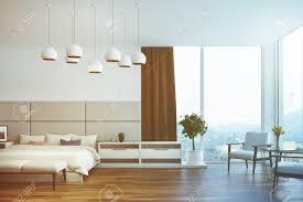 weiß und beige schlafzimmer interieur mit einem doppelbett mehrere nachttische sessel ein kleiderschrank aus holz und große fenster mit braunen