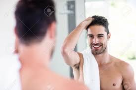 stattlicher mit nacktem oberkörper mann in den spiegel im badezimmer