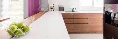 moderne küche mit kaffeemaschine auf glänzendem countertop und violetter heizung auf grauer wand
