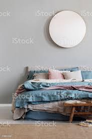 edle runde spiegel auf graue wand in stilvollen schlafzimmer interieur mit warmen bett mit blau pastell rosa und beige bettwäsche stockfoto und mehr