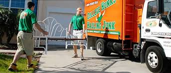 of College Hunks Hauling employees moving donated furniture into their truck