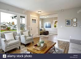 geräumiges wohnzimmer mit hellgrauen wände und große fenster