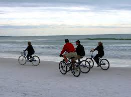 People Riding Bikes On The Beach Free Stock Photo