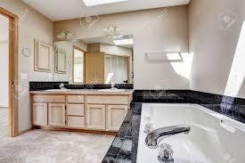 helles badezimmer interieur mit teppichboden weiße badewanne mit schwarzen granitfliesen trimmen waschbeckenunterschrank mit granitplatte und großem