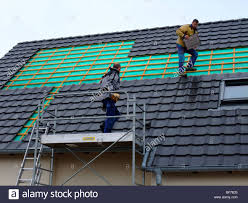 workers removing roof tiles to install photovoltaic solar panels