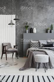 gestreiften teppich in grau schlafzimmer innenraum mit sessel neben bett gegen die betonwand echtes foto stockfoto und mehr bilder beton