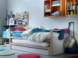 Trendy White Junior Bedroom With Orange Wall Mounted Bookshelf And Trundle Bed Paint
