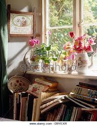 Close Up Of Summer Flowers In Pretty Vintage Jugs On Windowsill Above Pile Untidy