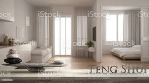 vintage holztisch regal mit stein balance und 3d buchstaben das wort fengshui über kleine wohnung mit küche wohnzimmer und schlafzimmer zen konzept
