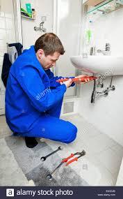ein klempner repariert defekte waschbecken im badezimmer